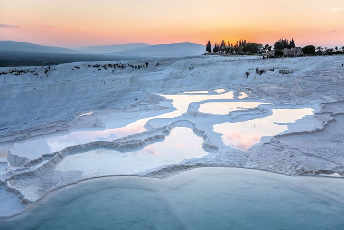 Overlooking the southwestern town of Pamukkale are its tiers of white limestone that shimmer beneath thermal ...