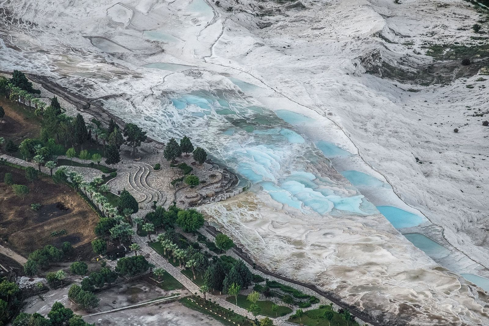 Aerial views of Pamukkale and its limestone thermal pools, taken in from a hot air balloon.