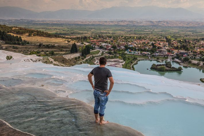A bather looks out across the protected pools towards the town of Pamukkale.