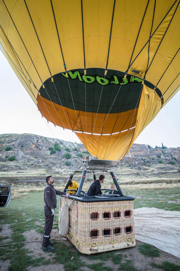 A man fires up a yellow hot air balloon at dawn.