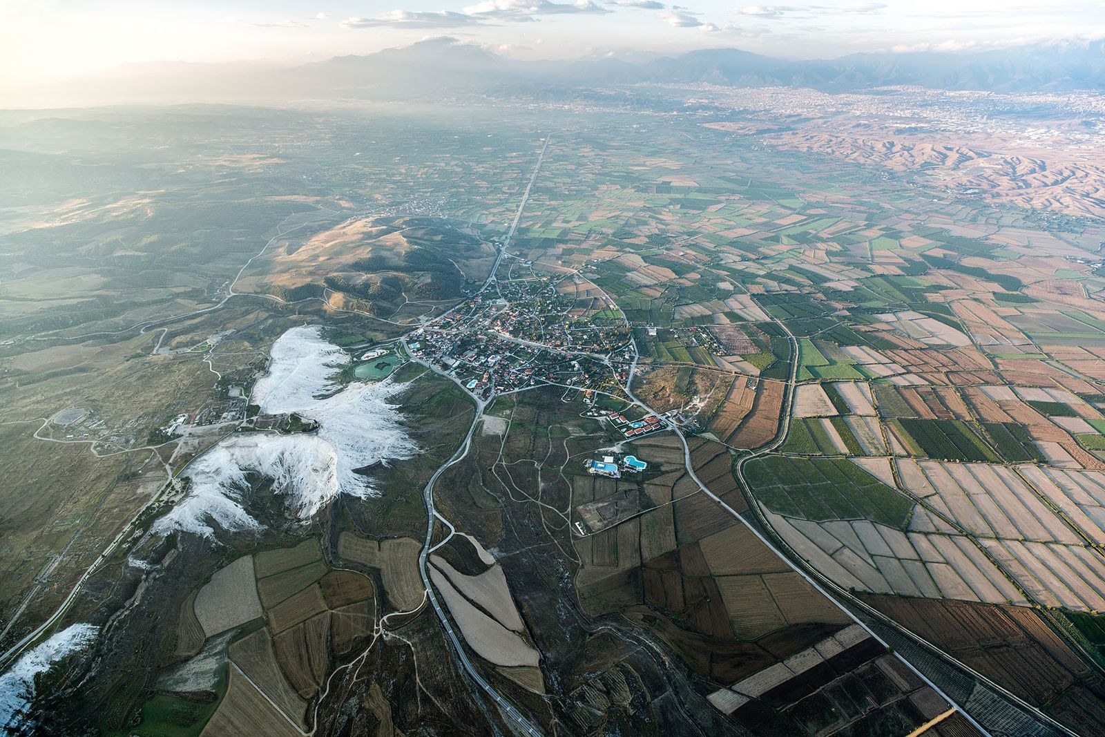 Pamukkale's patchwork of fields and thermal, limestone clusters as seen from the air.