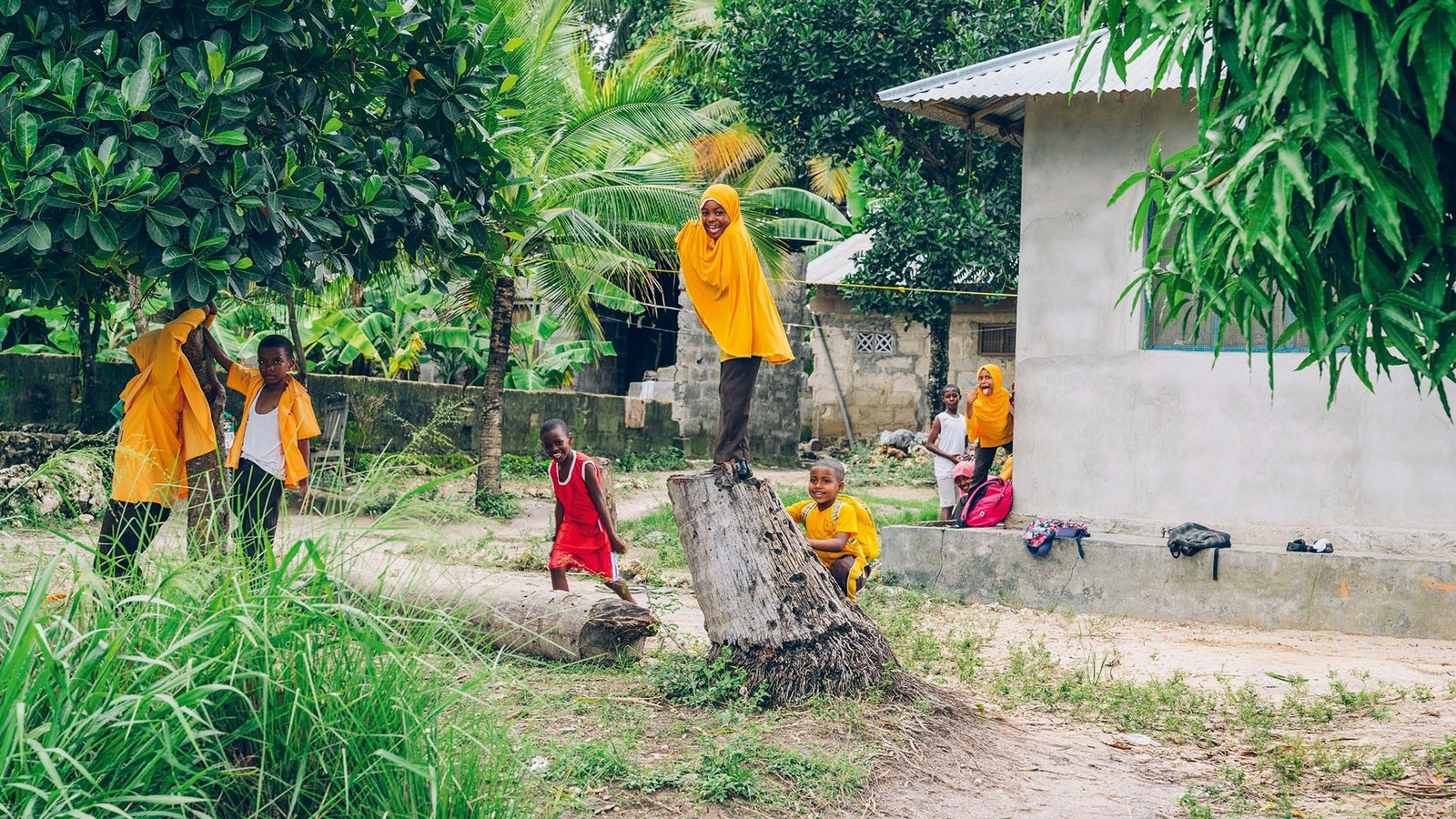 Children, some in their uniforms, playing outside after school, Pemba.