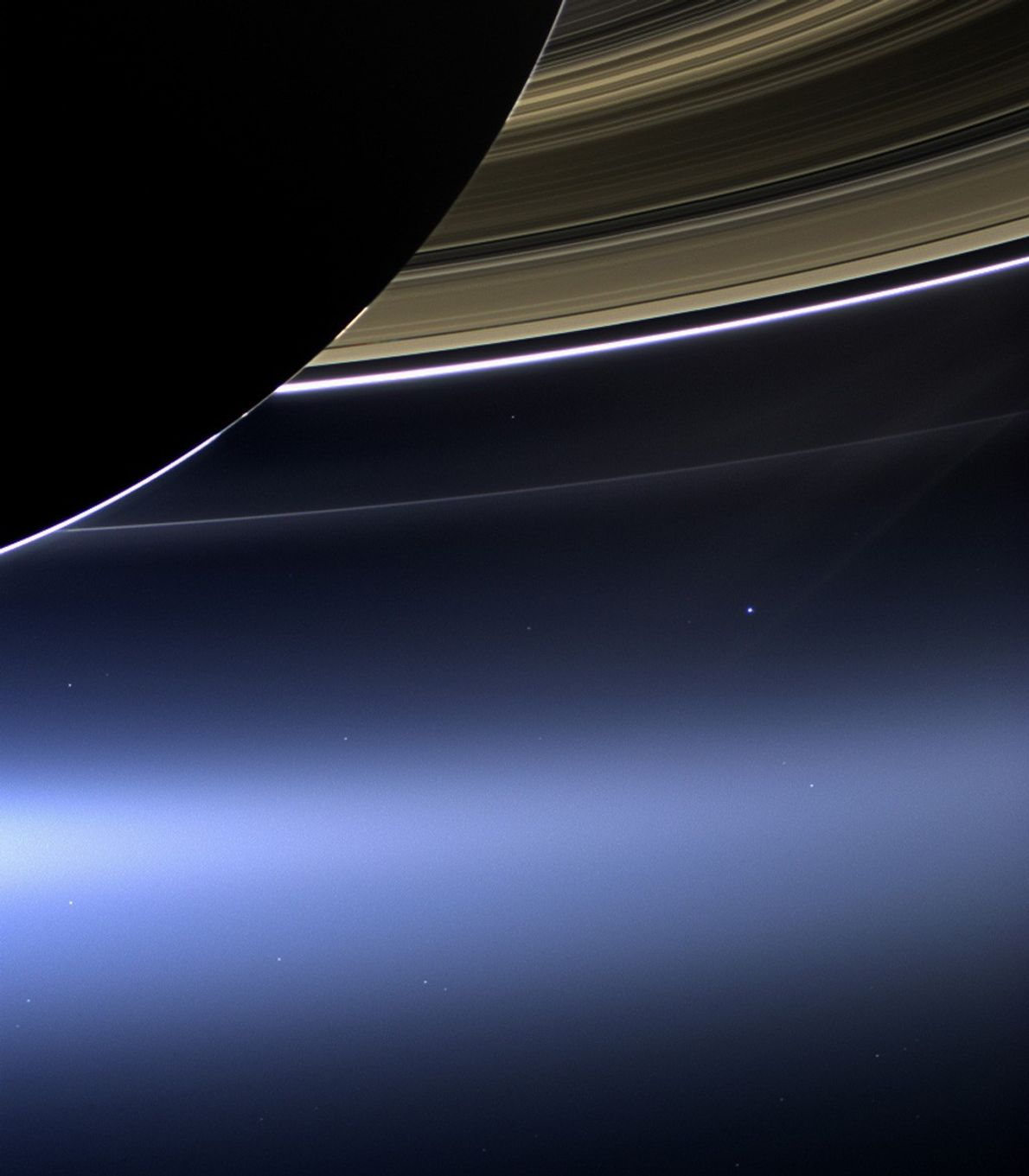 Earth seems to hover below the mighty rings of Saturn in a picture taken by the ...