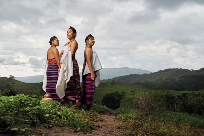 Women wear traditional huipil dresses and pozahuanco wraps.