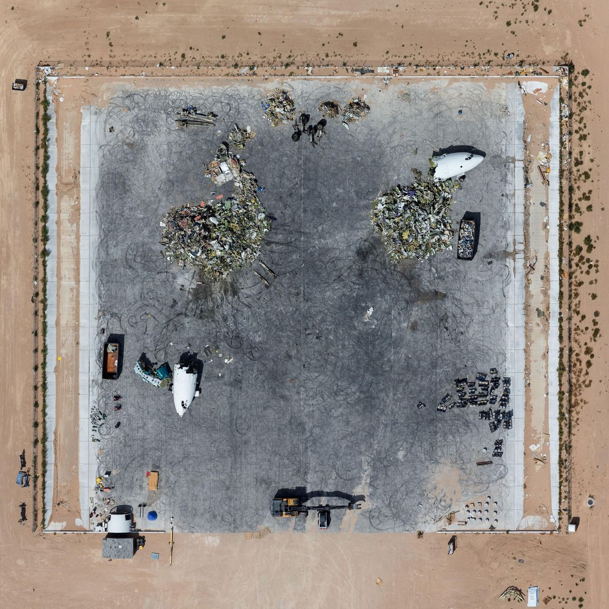 Aircraft are scrapped and shredded by heavy machinery in Victorville, California.