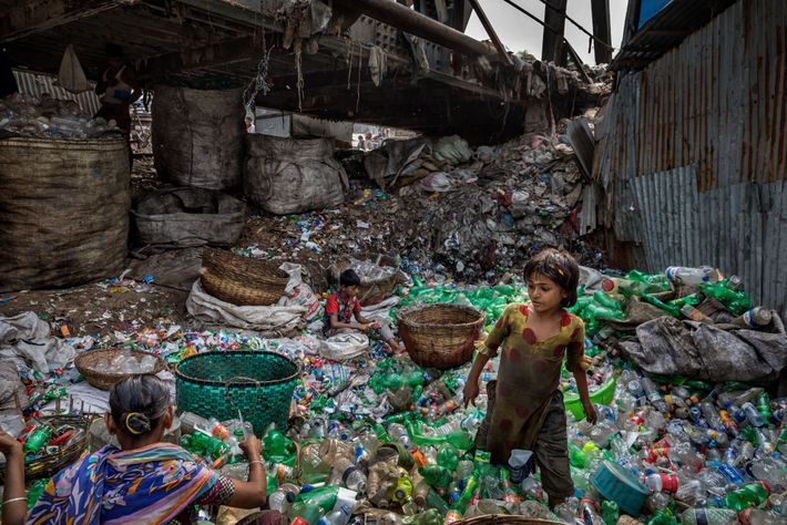 Under a bridge on a branch of the Buriganga River in Bangladesh, a family removes labels ...
