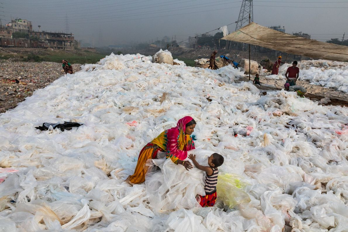 After sheets of clear plastic trash have been washed in the Buriganga River, in Dhaka, Bangladesh, ...