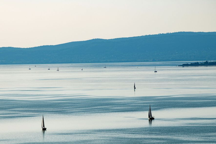 Mountains loom over Lake Balaton as the midday sunlight creates asilver canvas for the silhouettes of ...