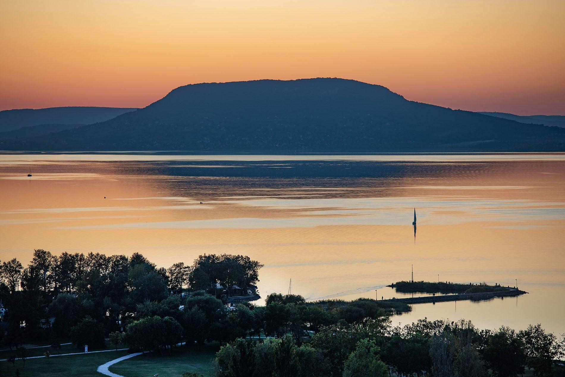 The view from the Millennium Lookout Tower, Gömbkilátó Balatonboglár, at sunset. Deep orangehues envelop the banks ...