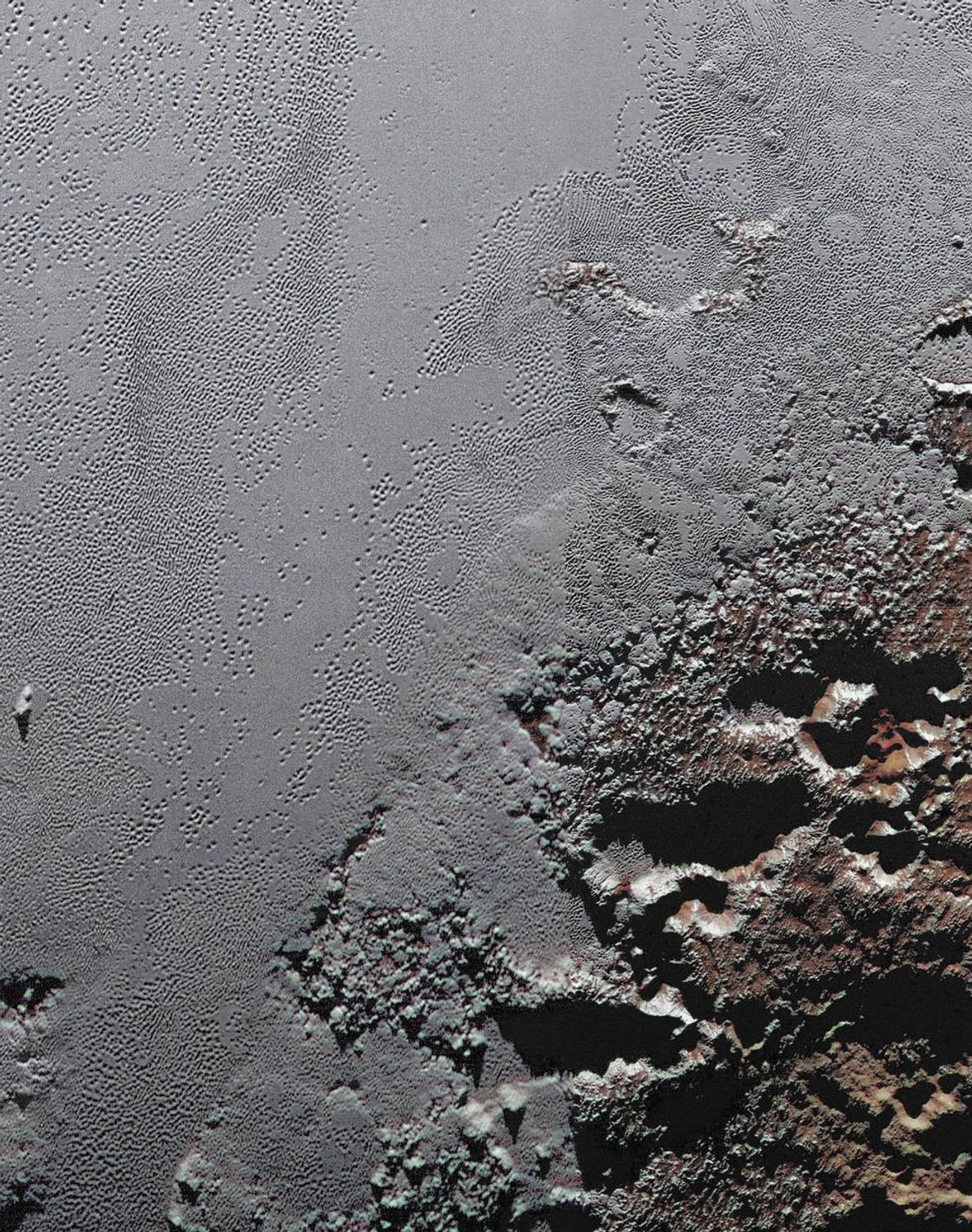 This dramatic image from NASA's New Horizons spacecraft shows the dark, rugged highlands known as Krun ...