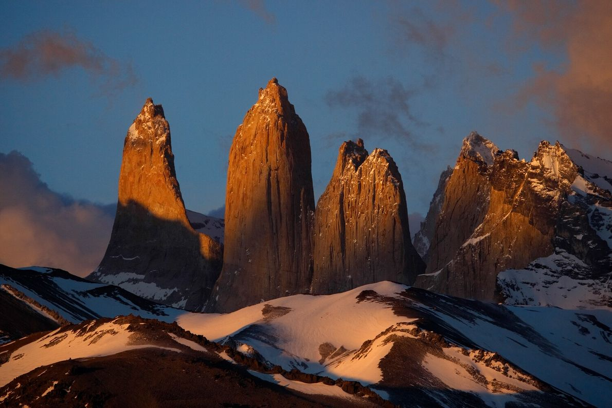 Sunlight glows on the impressive Torres del Paine in their namesake national park in Chile's Patagonia. The ...