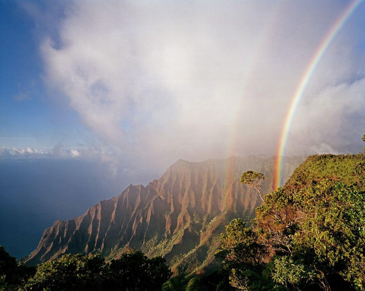 An iridescent double rainbow arcs over the Kalalau Valley on the Hawaiian island of Kauai. The ...