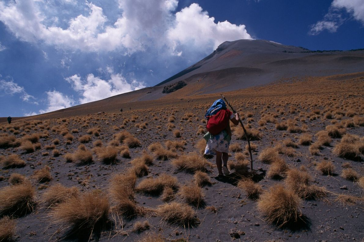 A woman climbs Popocatépetl, an active volcano in central Mexico, to make offerings to El Popo, ...