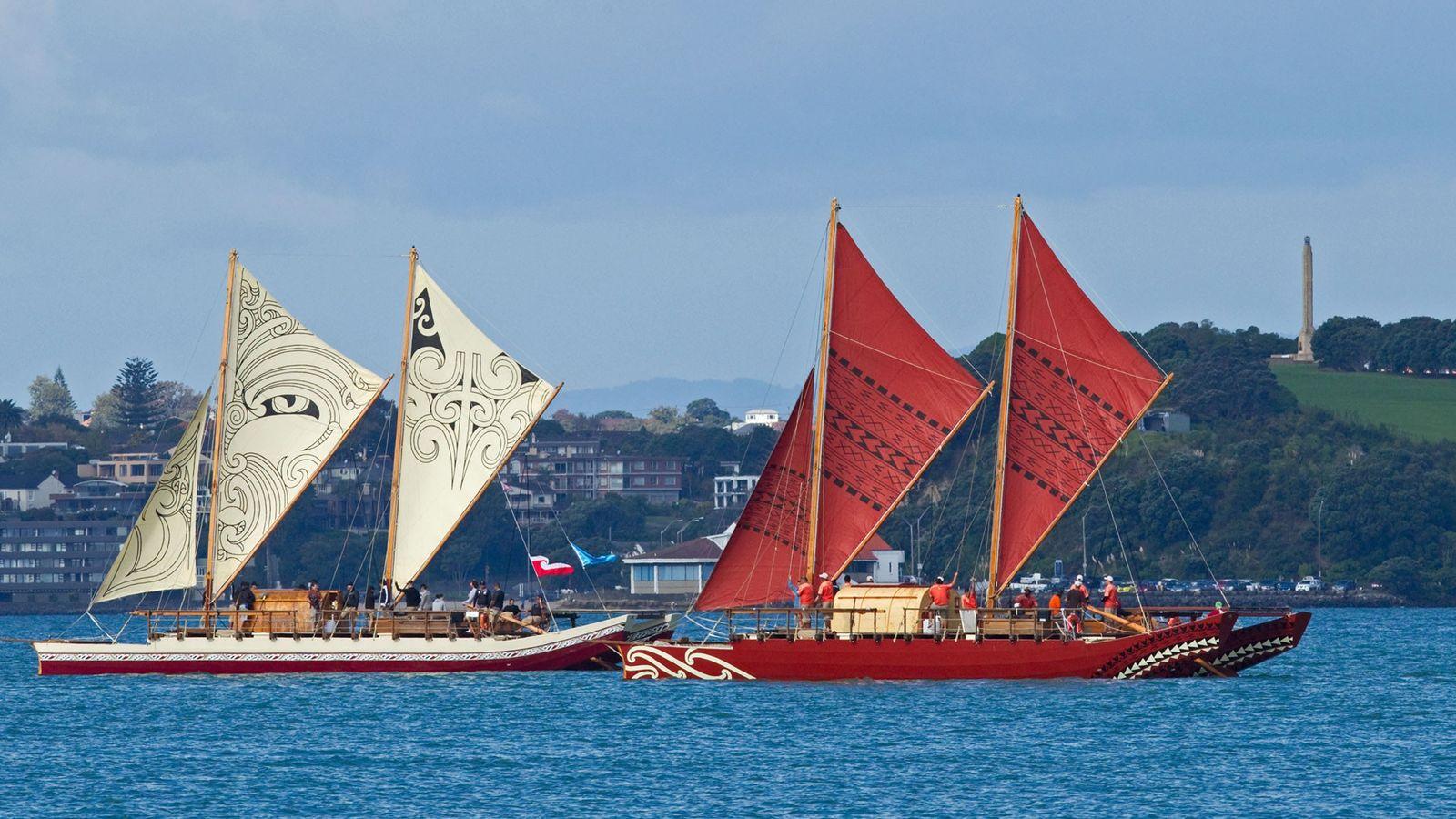 Two traditional, double-hulled waka, Te Matau a Maui (left) and Haunui (right), glide through the sea. ...