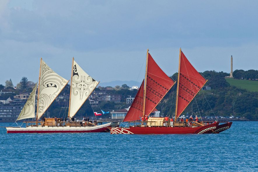 Two traditional, double-hulled waka, Te Matau a Maui (left) and Haunui (right), glide through the sea.