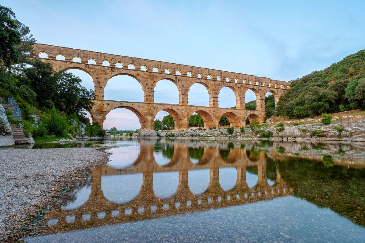 Arching over the Gardon River halfway between Nîmes and Uzès sits the massive Pont du Gard, ...