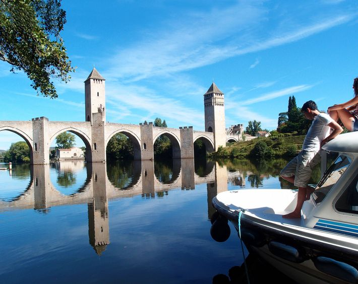 A boat approaches Pont Valentr, a 14th-century fortified stone arch bridge crossing the Lot River to ...
