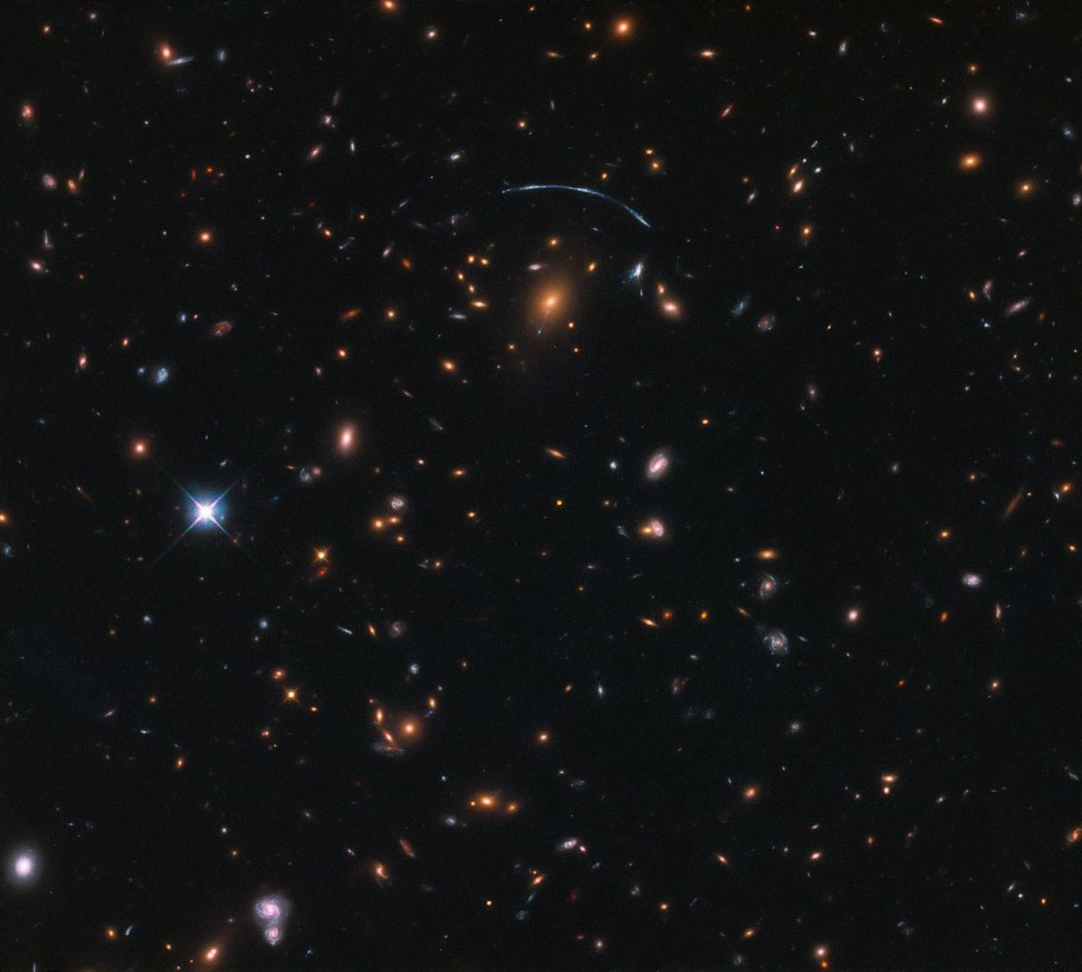 In this image, the gravitational influence of a massive galaxy cluster is causing a phenomenon called ...