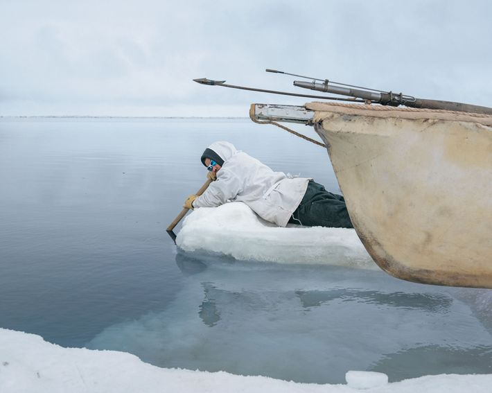 A hunter listens to the water for songs of nearby whales.