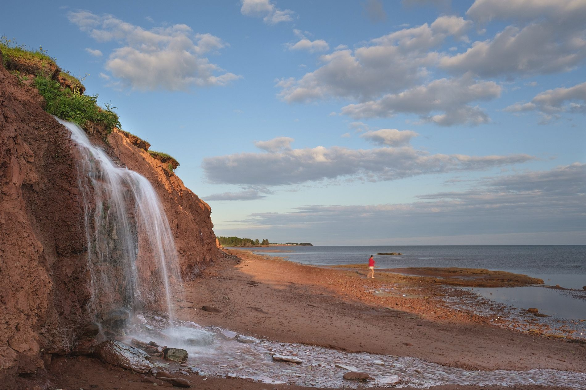 A spring flows out of a sandstone cliff, onto the beach, and into the Northumberland Strait ...