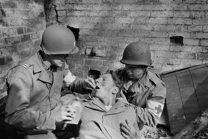 """An American soldier in WWII suffering from """"battle shock"""" is given a sedative by a medic. ..."""