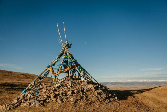 The moon and an ovoo or traditional shrine in Mongolia marks the mountain pass and the ...
