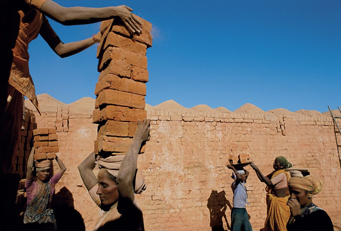 2002 , INDIA | In India, a family of debt labourers stack and haul bricks to ...