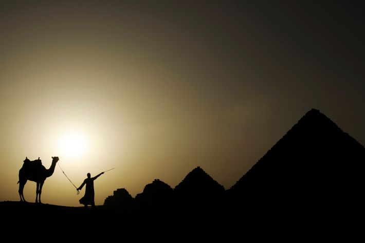 The sun sets over the Giza necropolis on the outskirts of Cairo, Egypt.