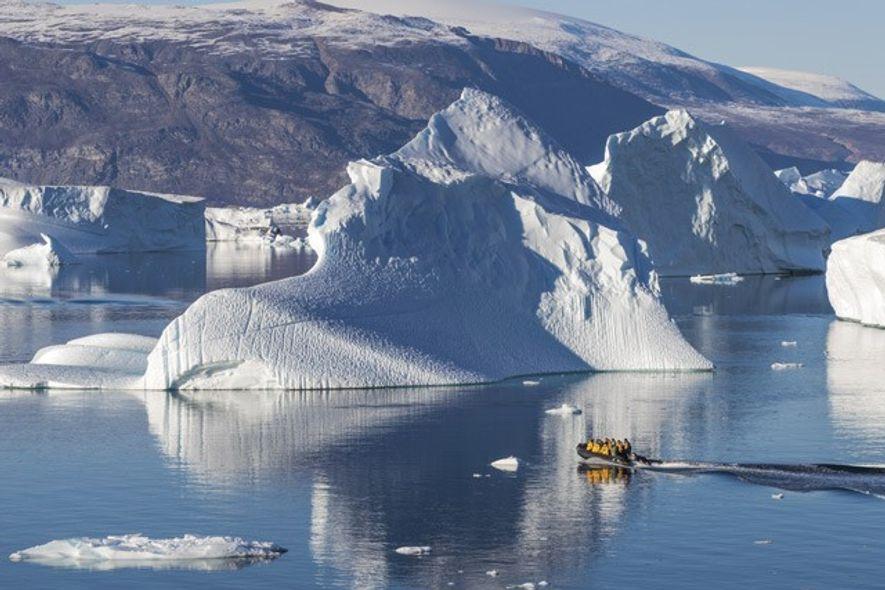 Icebergs dwarf a speedboat in Greenland