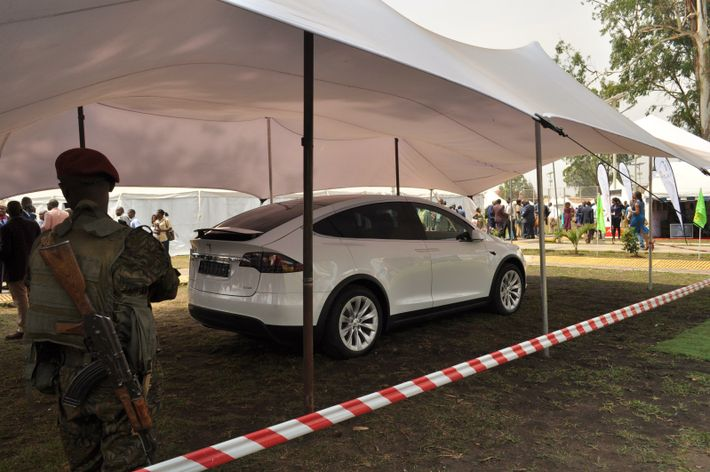 An armed soldier stands beside an electric car in Lualaba, Democratic Republic of Congo, during a ...