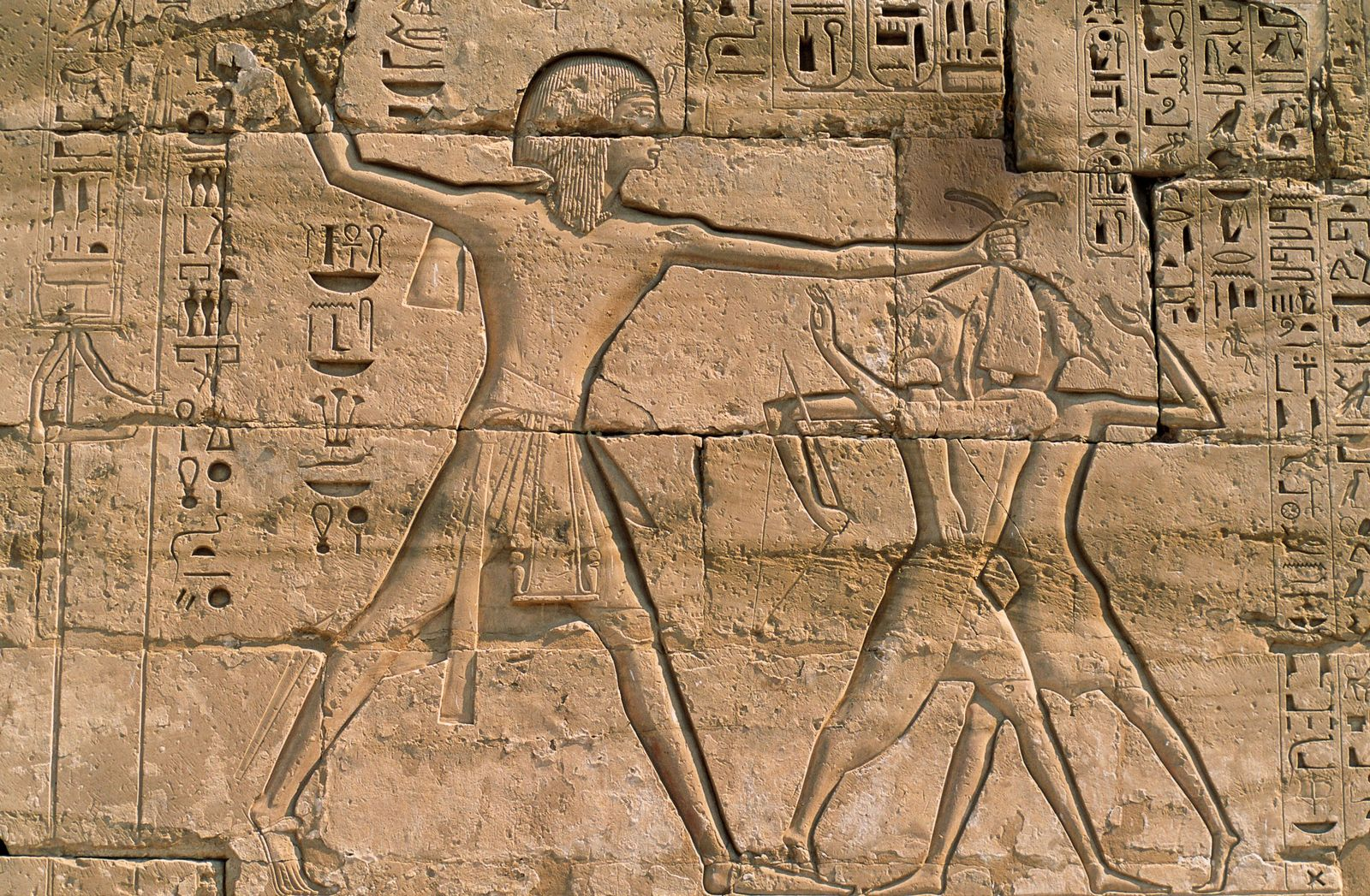 Standing tall, a vengeful Ramses III smites Sea People captives in a 12th-century B.C. relief at ...