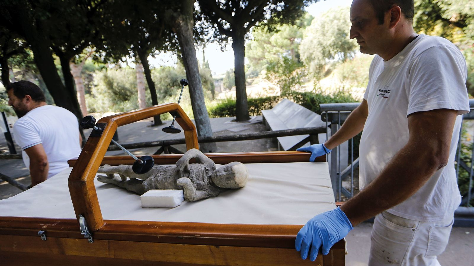Workers bear the remains of a young Pompeian boy, which will be undergoing DNA analysis. The ...
