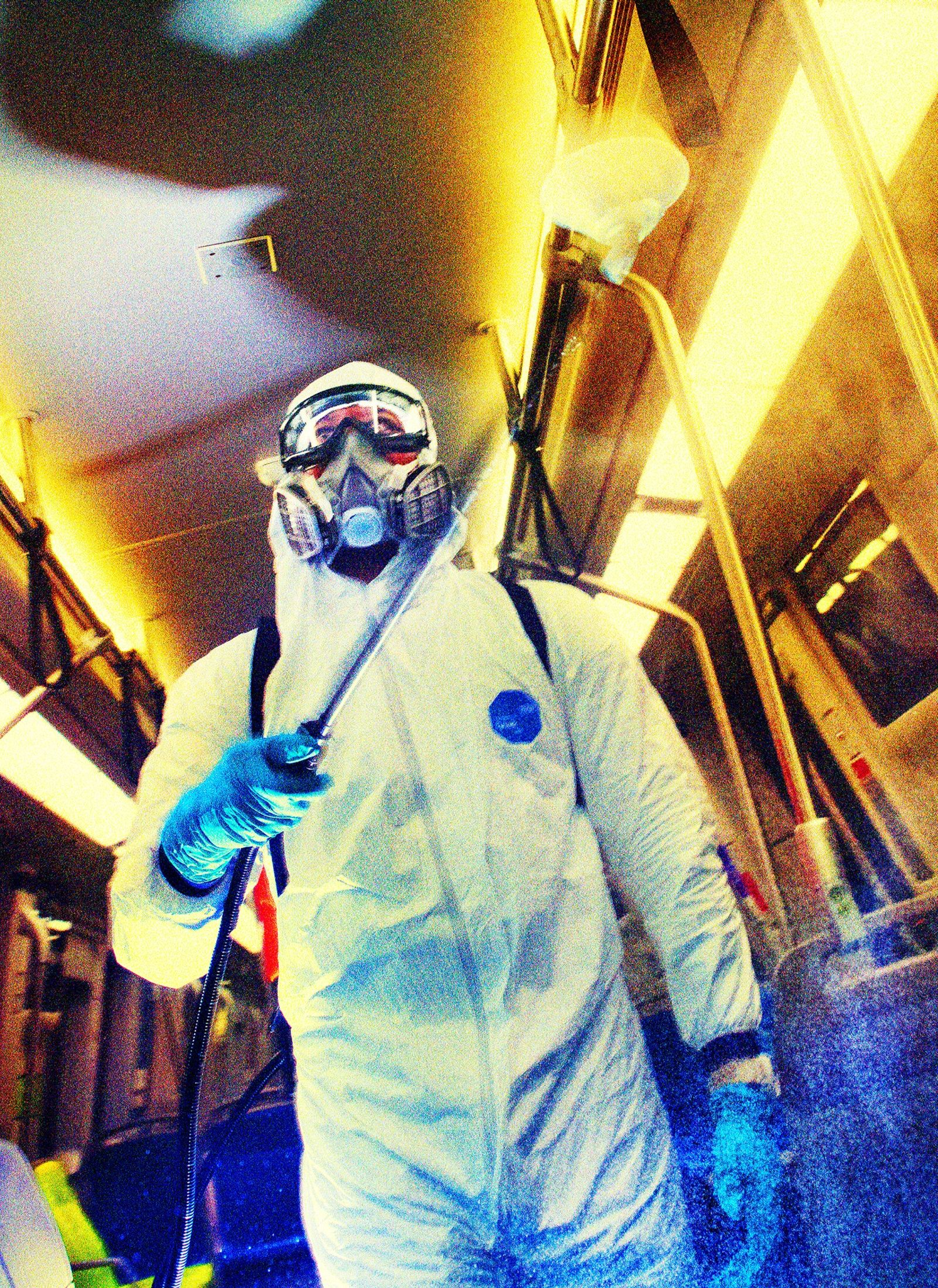 In full protective gear, Sterling Johnson sanitizes a Bay Area Rapid Transit train at a facility ...