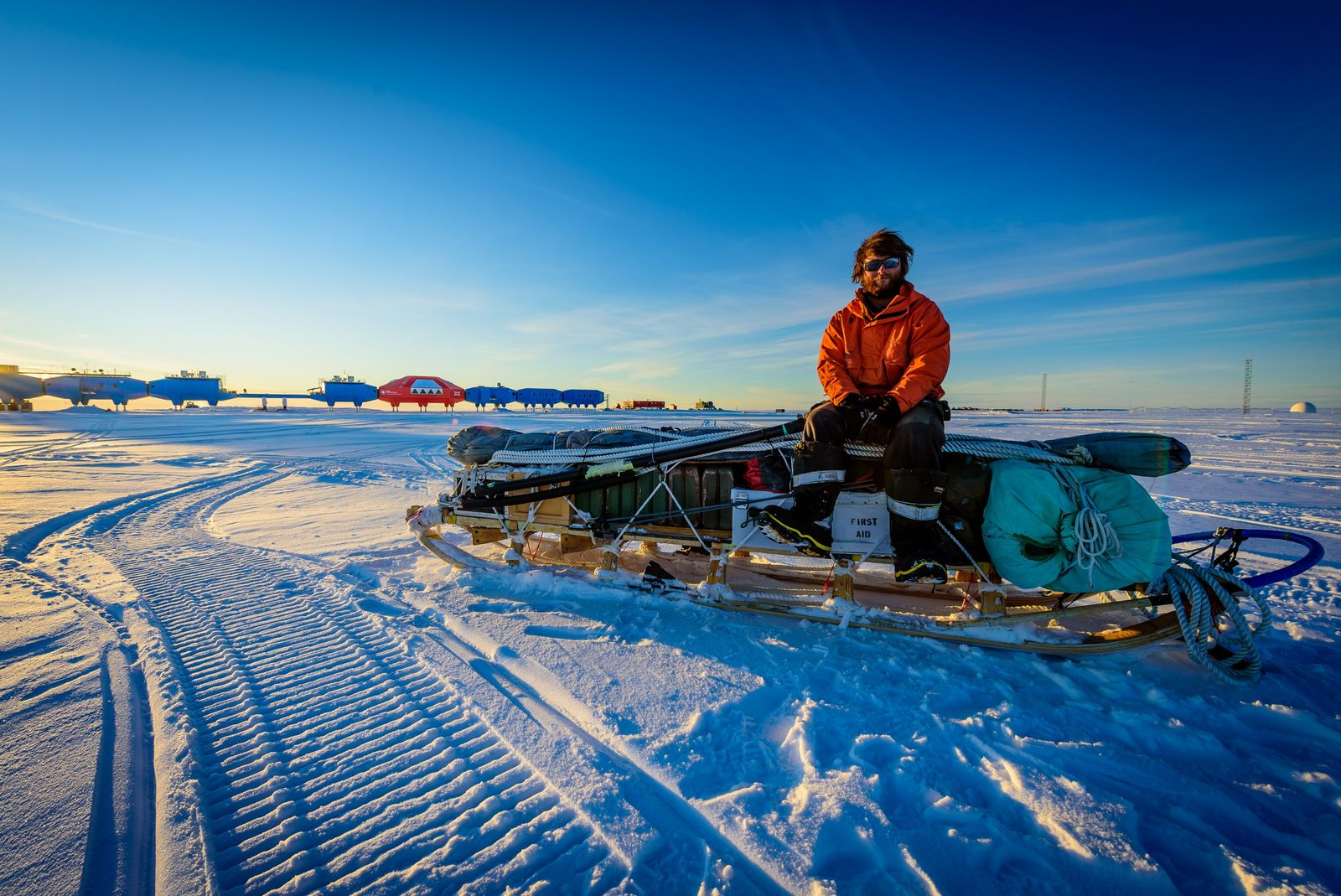 Richard Warren sits on a sled of supplies – with the otherworldly buildings of Halley VI ...