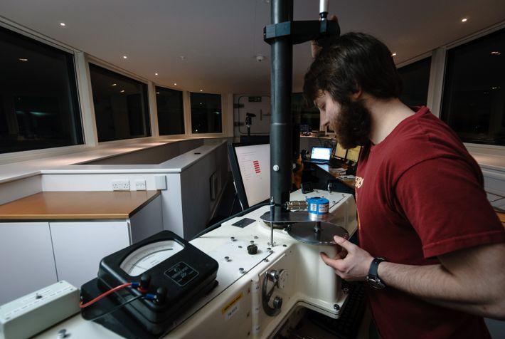 Darkness filling the ship-like windows of Halley VI, Richard Warren works on meteorological data.