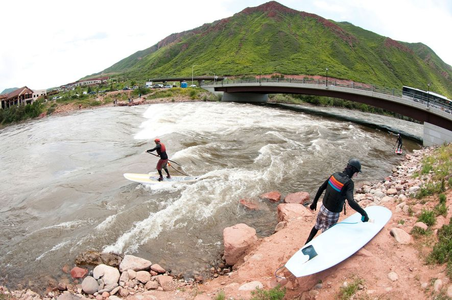 People surf the waves on the Colorado River near Glenwood Springs, Colorado.