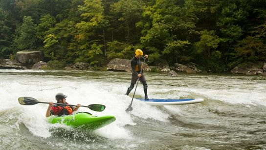 A surfer and kayaker ride a wave on the lower Gauley River near Fayatteville, West Virginia.