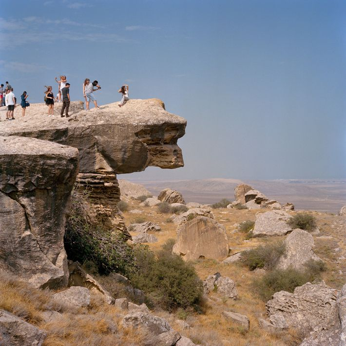 Visitors pose in the Gobustan Preserve, site of rock art dating back 40,000 years–and one of ...