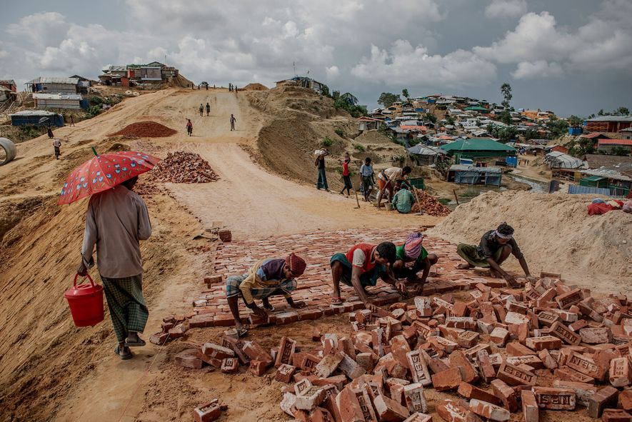 Refugees lay a brick road in the Balukhali camp, part of the expanded Kutupalong camp system.