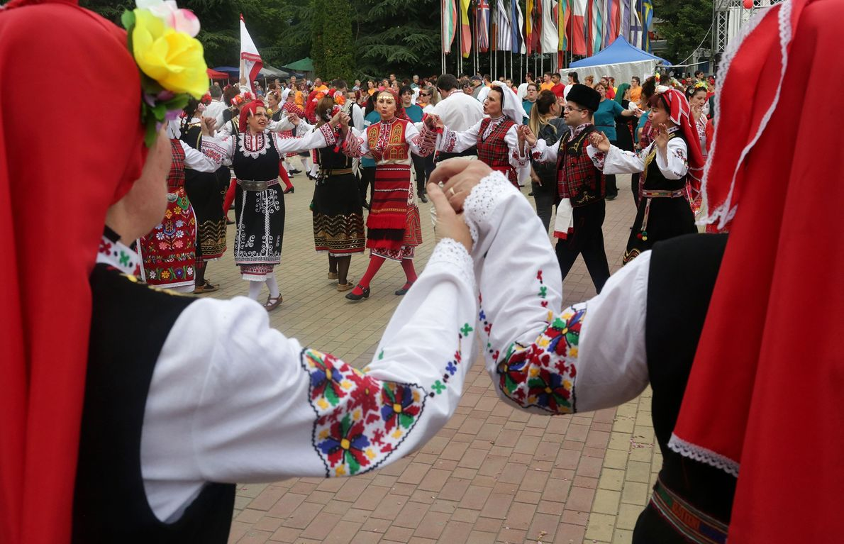 Men and women join hands for a traditional folk dance featuring subtle rhythms and intricate footwork.
