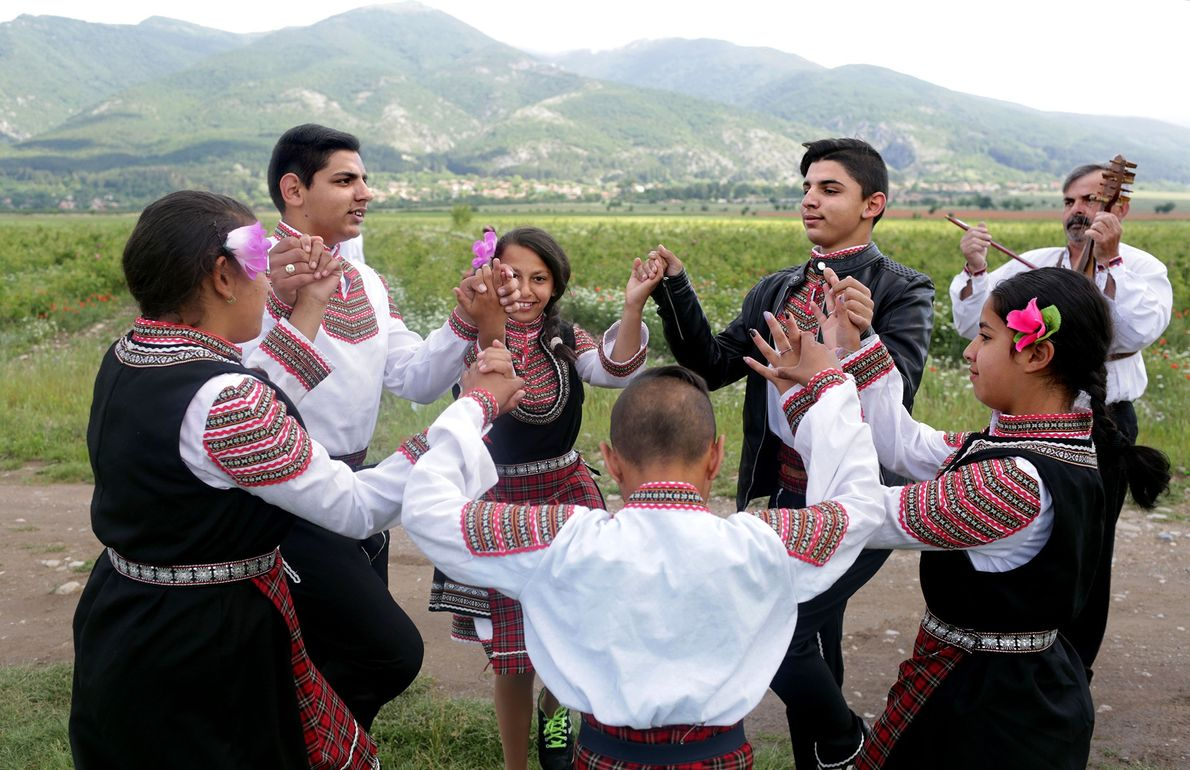 Children folk dance in rose fields during the annual festival.