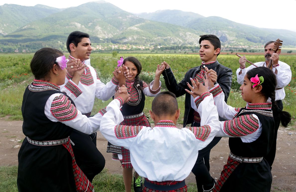 Children folk dance in rose fields during the annual festival.