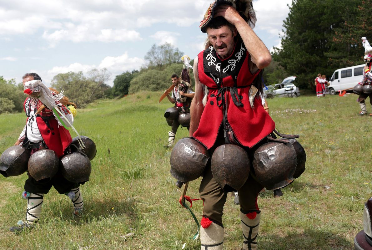 Men dressed as kukeri for the festival finish dancing. The traditional ritualistic dance intends to scare ...