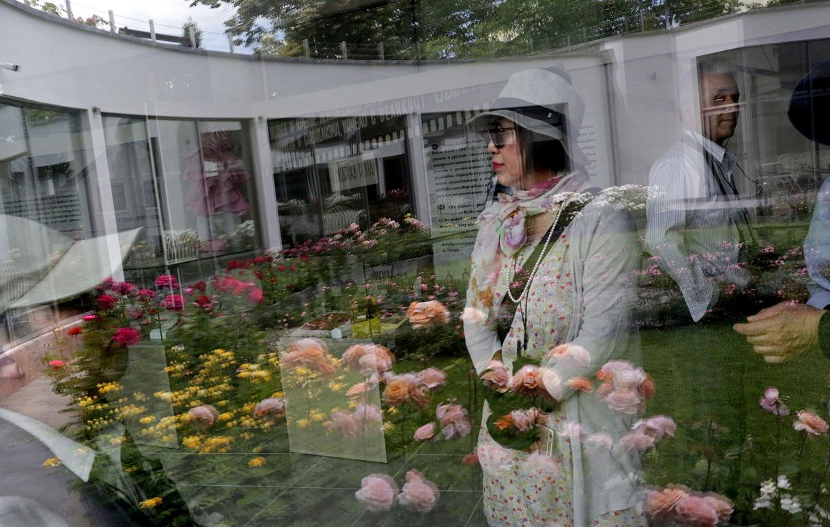 Tourists' reflections are seen on a window at the Rose Museum, located in the Park Rose ...