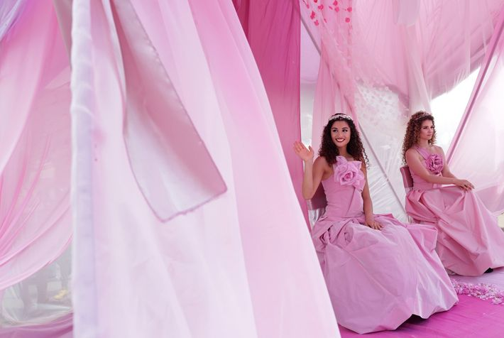 Rose Queen Mihaela Hadzhieva waves from centre stage on her pink throne during the parade.