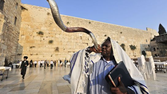 A man blows a shofar horn at the Western Wall Plaza in Jerusalem's Old City to ...