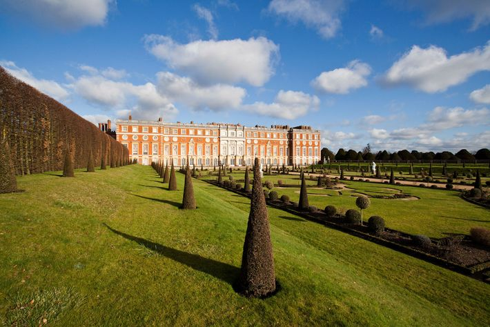 Hampton Court Palace, a beloved leisure retreat for many monarchs, stands above its formal gardens in ...