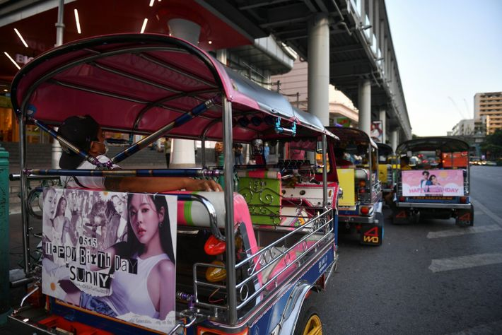 Tuk-tuk drivers, with their vehicles decorated with banners of K-pop stars, wait for customers in Bangkok