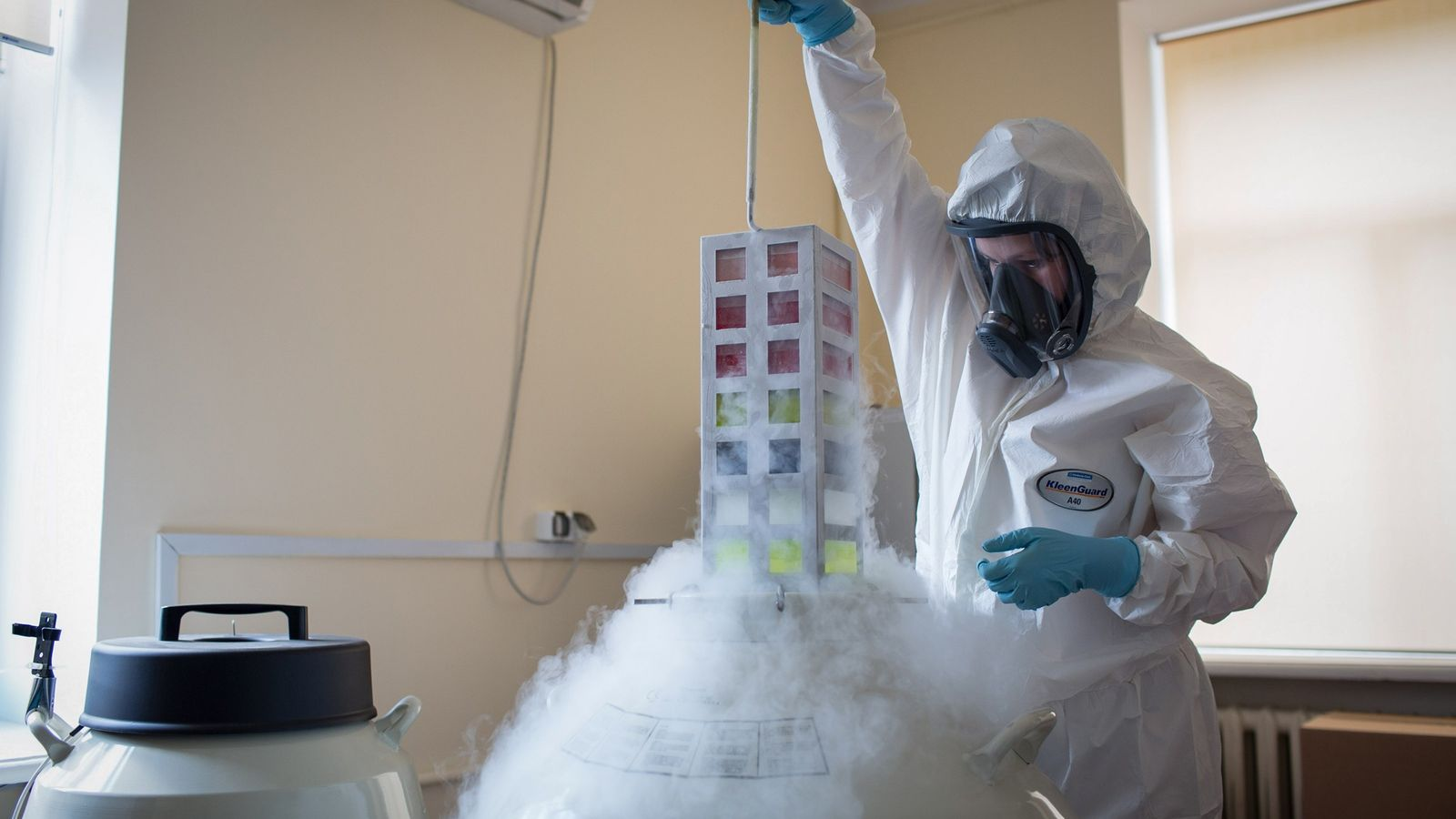 A lab technician removes a vaccine bank from cryostorage on August 6, 2020, during production of ...