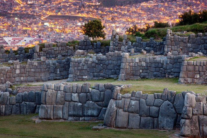 The ancient fortress of Sacsayhuam contrasts with modern buildings in Cusco, Peru.